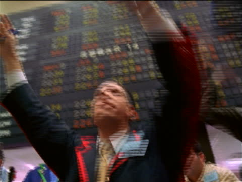 vídeos de stock, filmes e b-roll de low angle close up pan 2 male traders shaking arms + shouting beneath display board / commodity exchange, nyc - panning