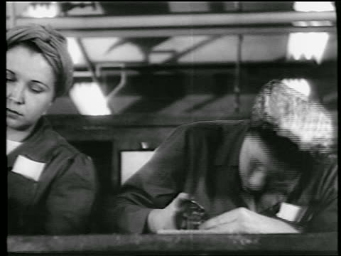 stockvideo's en b-roll-footage met b/w 1944 low angle close up 2 women with kerchiefs on heads riveting in defense plant / world war ii / industrial - first line of defense filmtitel