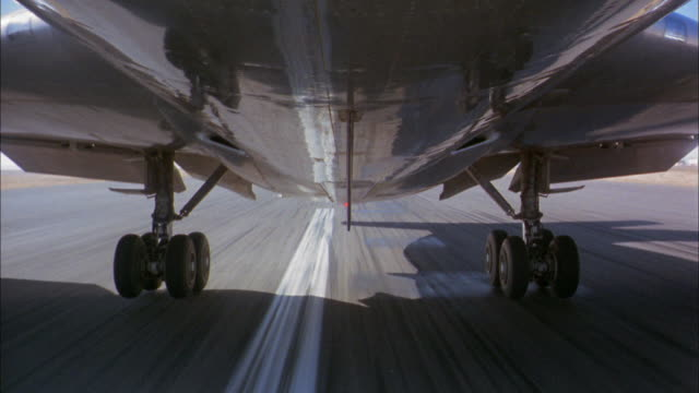 low angle close up 707 jet plane wheels lifting during take off and landing gear folding in during flight - 滑走路点の映像素材/bロール