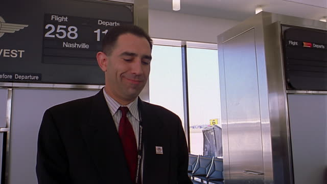 Low angle close up airline worker checking passenger's ticket at gate