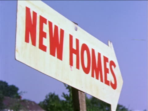 "vídeos de stock e filmes b-roll de 1959 low angle close up arrow shaped sign with red lettering ""new homes"" / blue sky + trees in background / phila. / docu. - 1950 1959"