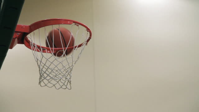low angle, close up basketball hoop in gymnasium; multiple basketball shots; some bounce off backboard or rim; other shots are swished or bounce through the hoop and net. - shooting baskets stock videos and b-roll footage