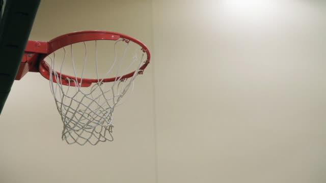 Low angle, close up basketball hoop in gymnasium; multiple basketball shots; some bounce off backboard or rim; other shots are swished or bounce through the hoop and net.