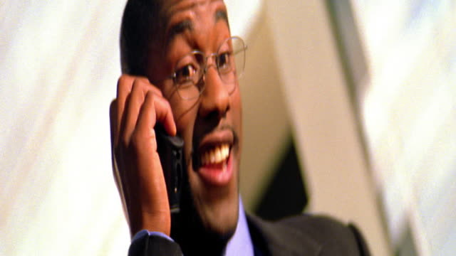 low angle close up black businessman with eyeglasses talking on cellular phone indoors / toronto - one mid adult man only stock videos & royalty-free footage