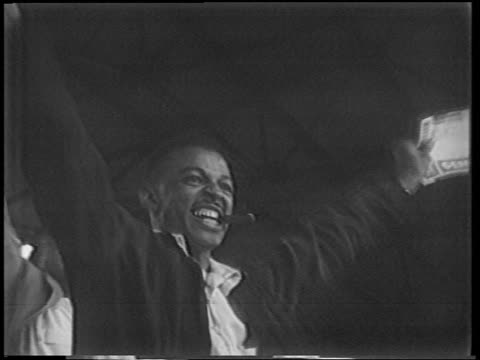 vídeos y material grabado en eventos de stock de b/w 1951 low angle close up black man in audience smoking cigar raising arms in excitement / playoffs - 1951