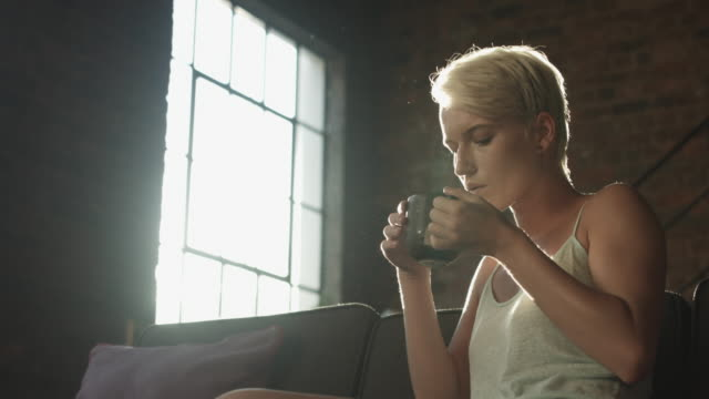 vídeos y material grabado en eventos de stock de low angle close up, blonde woman drinks coffee in morning - cabello corto