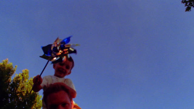 low angle close up boy on man's shoulders holding pinwheel outdoors - girandola video stock e b–roll