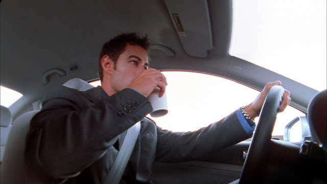 Low angle close up businessman drinking coffee while driving car