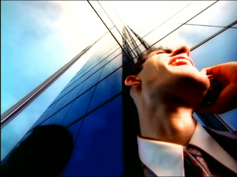 vidéos et rushes de overexposed low angle close up businessman talking, laughing + shouting on cellular phone by mirrored building - overexposed