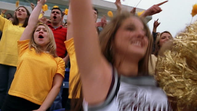 low angle close up cheerleaders with gold pom poms cheering / crowd jumping and cheering in background - ncaa college football stock videos and b-roll footage