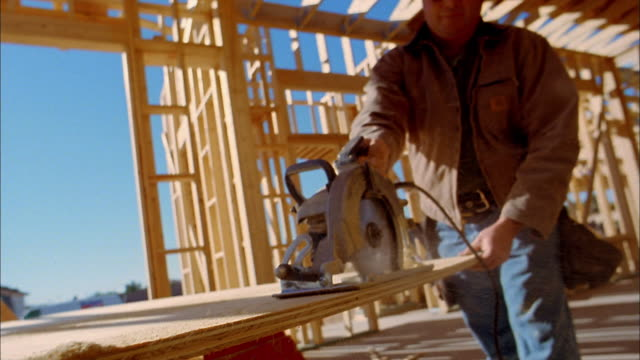low angle close up construction worker cutting board w/circular saw / phoenix, arizona - baugerät stock-videos und b-roll-filmmaterial