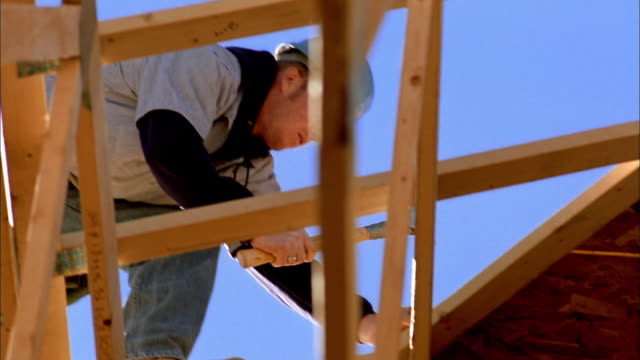 vidéos et rushes de low angle close up construction worker hammering on house frame / phoenix, arizona - ouvrier du bâtiment
