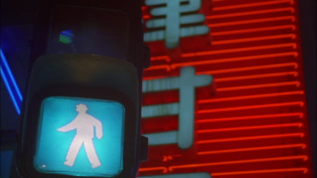 Low angle close up crosswalk sign changing from 'Walk' to 'Don't Walk' with flashing neon sign in background / Tokyo, Japan
