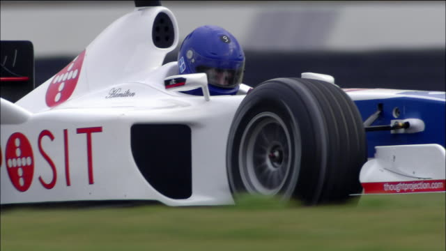 low angle close up driver of formula race car steering around s curve - automobilismo video stock e b–roll