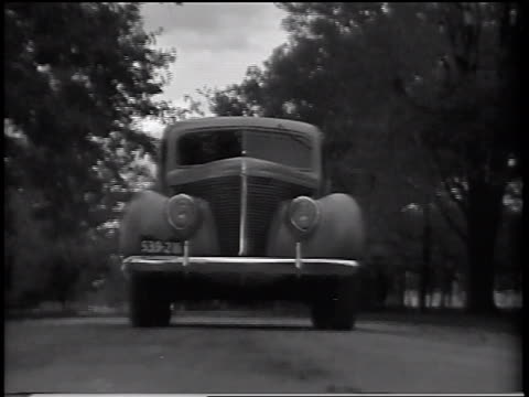 B/W 1937 low angle close up Ford V-8 Standard sedan driving on road over camera / commercial