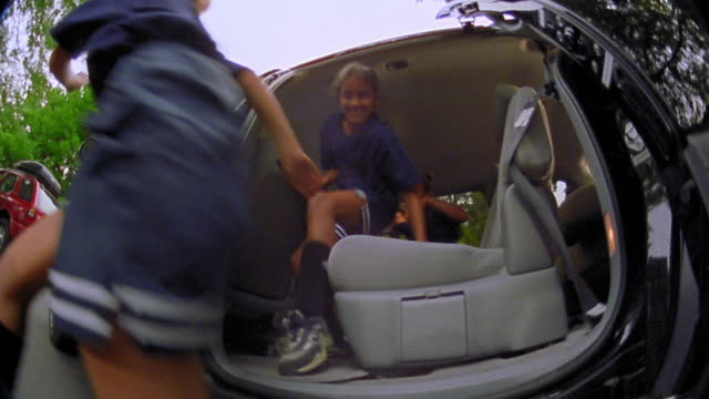 FISHEYE low angle close up four girls in soccer uniforms getting out of minivan with woman watching