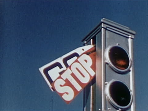 "1952 low angle close up ""go"" sign lowering and ""stop"" sign raising on old-fashioned traffic signal / AUDIO"