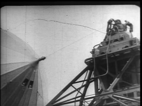 b/w 1937 low angle close up hindenburg slowly being pulled into mooring by cable attached to nose / new jersey - ヒンデンブルク号点の映像素材/bロール