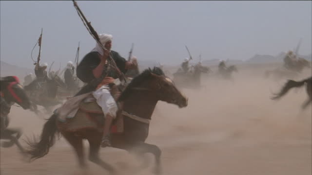 low angle close up horse hooves kicking up dust / tilt up zoom out men racing across desert on horseback - herbivorous stock videos & royalty-free footage