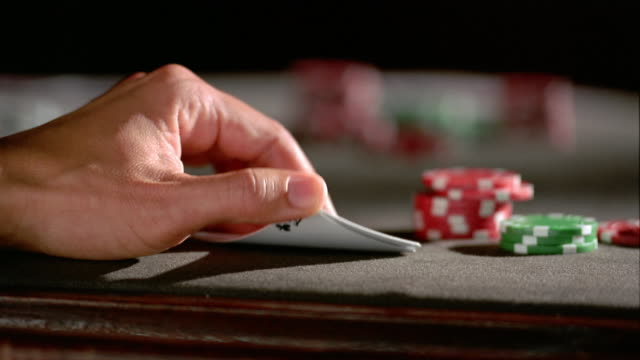 Low angle close up lifting card hand off table with thumb / revealing ace of clubs