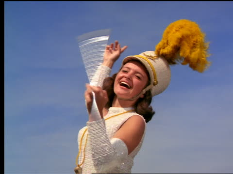 stockvideo's en b-roll-footage met 1964 low angle close up majorette twirling baton + smiling outdoors - prestatie