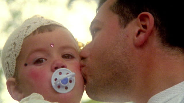 vídeos de stock e filmes b-roll de low angle close up man holding and kissing young girl in costume with pacifier in mouth outdoors / provence, france - super exposto