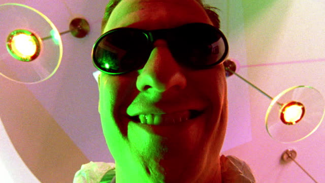 """vídeos de stock, filmes e b-roll de low angle close up man in sunglasses smiling moves off camera, reveals """"digitize everything"""" projected on ceiling - escrita ocidental"""