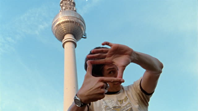 Low angle close up man making frame with fingers with Fernsehturm in background / Berlin, Germany