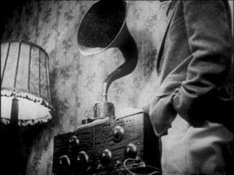 stockvideo's en b-roll-footage met b/w 1927 low angle close up man standing by early radio / newsreel - 1920