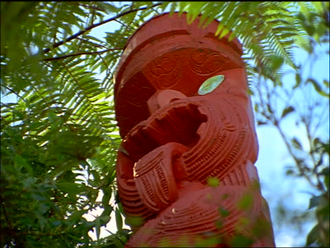 low angle close up Maori totem sculpture of face with tounge sticking out / Rotorua, North Island, New Zealand