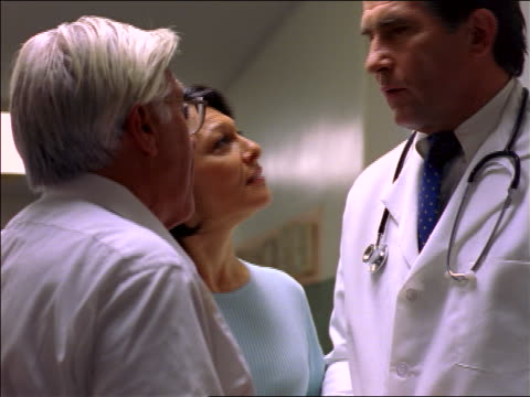 vídeos de stock, filmes e b-roll de low angle close up middle-aged doctor talking to worried senior man + woman in hospital corridor / they smile - preocupado