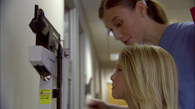vidéos et rushes de low angle close up nurse weighing young boy and measuring his height - mesurer