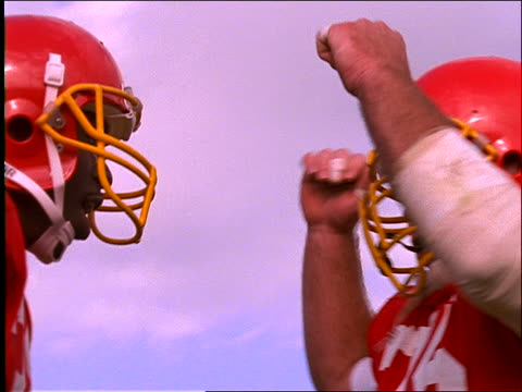 """low angle close up of 2 football players pounding shoulders and pushing / Getting """"pumped up"""""""