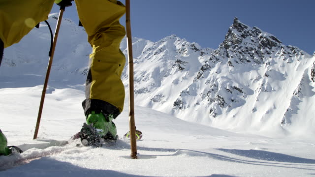 low angle close up of a man skinning with big mountians in background - ski stock videos & royalty-free footage