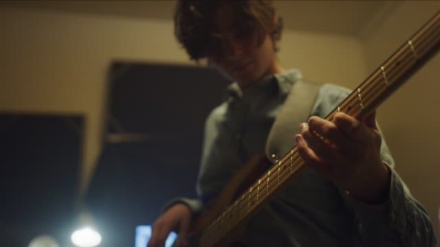 low angle close up of man playing bass guitar in music studio / provo, utah, united states - エレキギター点の映像素材/bロール