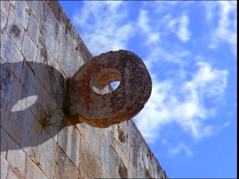 low angle close up of time lapse clouds in sky over circular goal used in ancient pok-a-tok game on mayan ruins / mexico - mayan stock videos & royalty-free footage