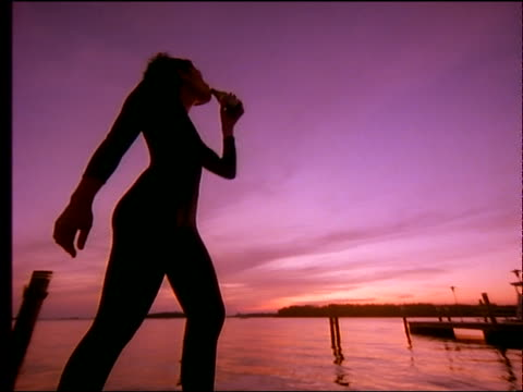 low angle close up of woman drinking from bottle by lake / sunset