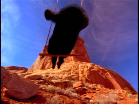 vidéos et rushes de low angle close up of woman on swing with desert rock formations in background - cinématographie