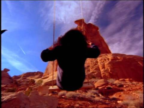low angle close up of woman on swing with desert rock formations in background - südwestliche bundesstaaten der usa stock-videos und b-roll-filmmaterial