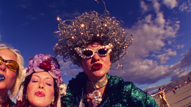 low angle close up pan three women in gaudy costumes and wigs making faces at camera outdoors - eccentric stock videos & royalty-free footage