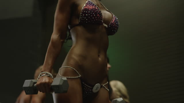 Low angle close up panning shot of bodybuilder lifting weights before competition / Draper, Utah, United States