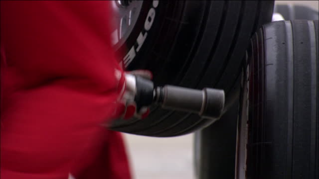 low angle close up pit crew member holding lug gun / formula one race car tire being changed - sheppard132点の映像素材/bロール