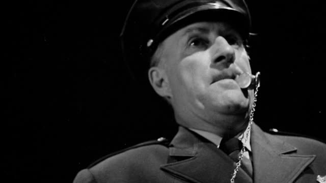 b/w low angle close up policeman with whistle in mouth raising hand with black background - trillerpfeife stock-videos und b-roll-filmmaterial