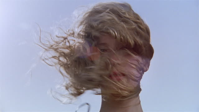 vidéos et rushes de low angle close up portrait of woman with hair blowing in wind - wind
