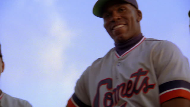 low angle close up PAN PORTRAIT three smiling Black, Asian, + Caucasian baseball players standing outdoors