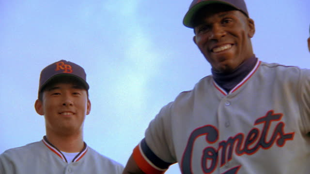 low angle close up PAN PORTRAIT three smiling Black, Asian, + Causcasian baseball players standing outdoors