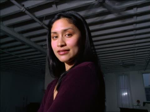 vídeos de stock, filmes e b-roll de low angle close up portrait woman standing in loft smiling at camera / ceiling fans in background - ventilador de teto