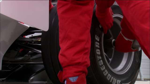 low angle close up rear tire of formula one race car being changed by pit crew - formula one racing stock videos & royalty-free footage