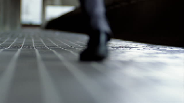 stockvideo's en b-roll-footage met low angle close up selective focus feet of man running on paved walkway - ontsnappen