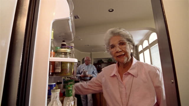 low angle close up senior woman opening refrigerator door and taking out jug of milk with senior man in background - milk jug stock videos & royalty-free footage